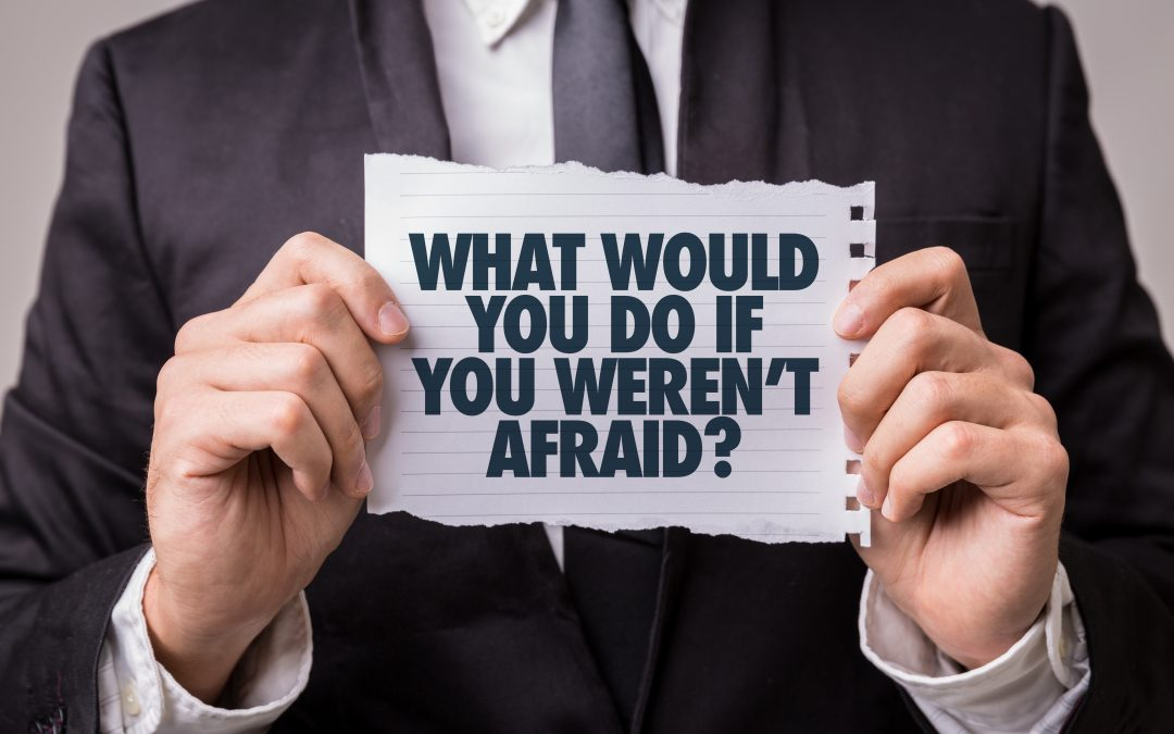 close up of a person wearing a suit holding a piece of paper that says 'what would you do if you weren't afraid?'